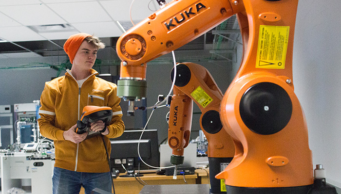 Studemt operates robotic arm in UFV Autotomation and Robotics lab